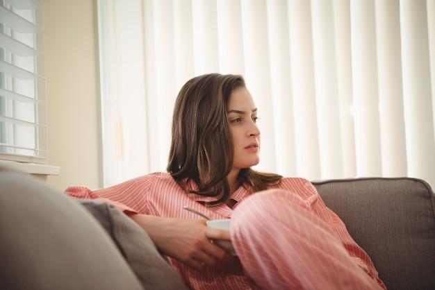 Kobieta odwraca wzrok siedząc na kanapie przed zasłonami
