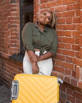 Kobieta odwraca wzrok, trzymając jej żółty bagaż
