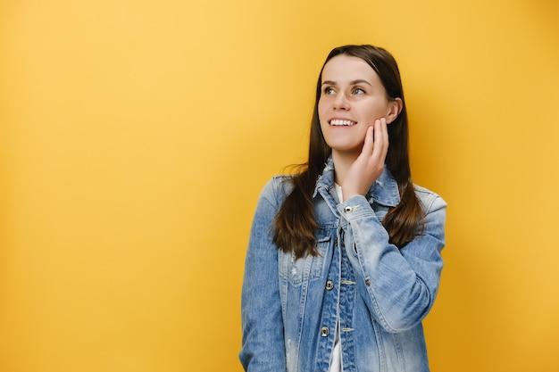 Kobieta odwraca wzrok z szerokim uśmiechem dotyka policzka