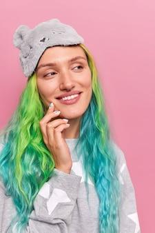 Kobieta odwraca wzrok z zadowoloną miną farbowane włosy przypominają sobie coś przyjemnego nosi na czole maskę do spania piżama uśmiecha się delikatnie pozuje na różowo