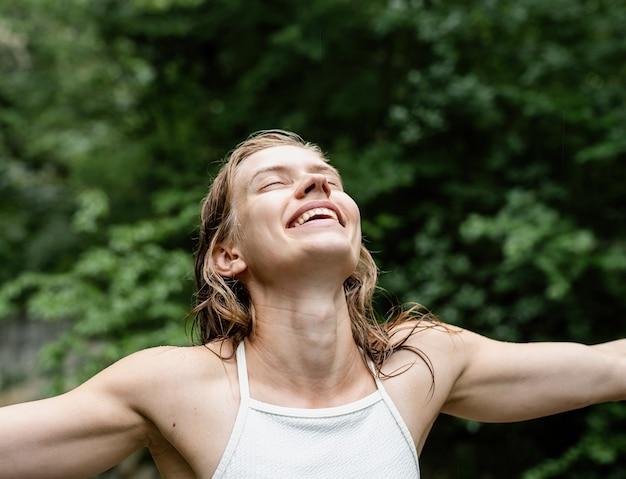 Kobieta odwracająca twarz do nieba i śmiejąca się z zamkniętymi oczami