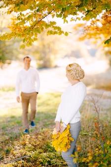 Kobieta odwróciła się do zbliżającego się mężczyzny, trzymającej w dłoniach wieniec z żółtych liści