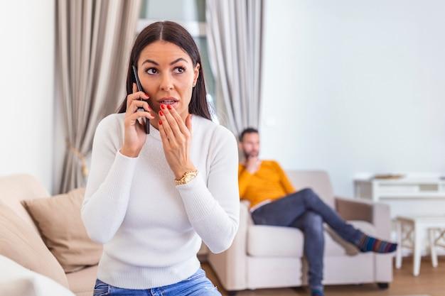 Kobieta odwróciła się plecami do mężczyzny, rozmawiając przez telefon ze swoim kochankiem, chłopakiem siedzącym z tyłu przed telewizorem.
