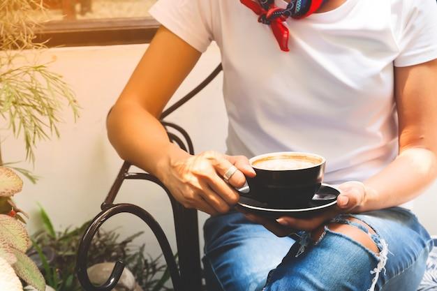 Kobieta odziewa pije kawę w przypadkowego stylu odzieży, stylu życia kobiety pojęcie