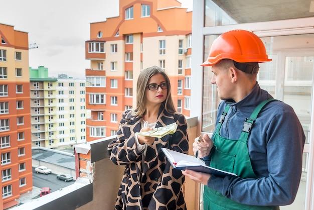 Kobieta oferuje banknoty dolara konstruktorowi na budowie