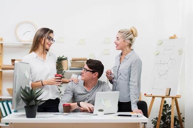 Kobieta oferuje kawę mężczyzna przy biurem