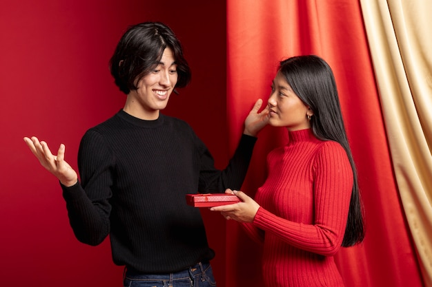 Kobieta oferuje prezent dla mężczyzny na chiński nowy rok