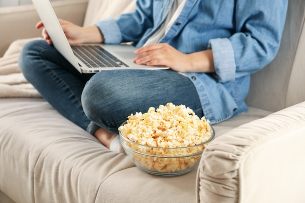 Kobieta ogląda film na kanapie i je popcorn. jedzenie do oglądania filmów