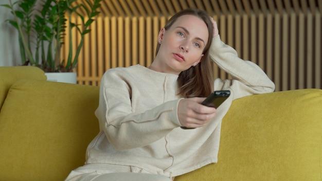 Kobieta ogląda filmy na ekranie telewizora w swoim domu, przełącza kanały pilotem siedząc na żółtej sofie w salonie