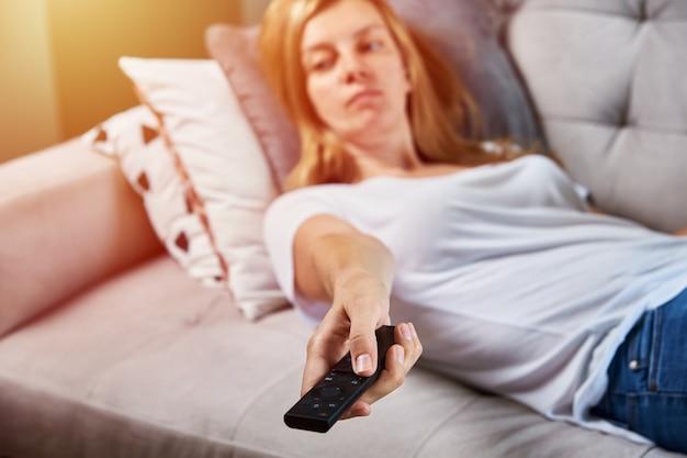 Kobieta ogląda telewizor na kanapie i przełącza kanały za pomocą pilota