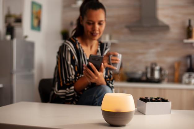 Kobieta ogląda wideo na telefonie i cieszy się parą z olejkami eterycznymi z dyfuzora