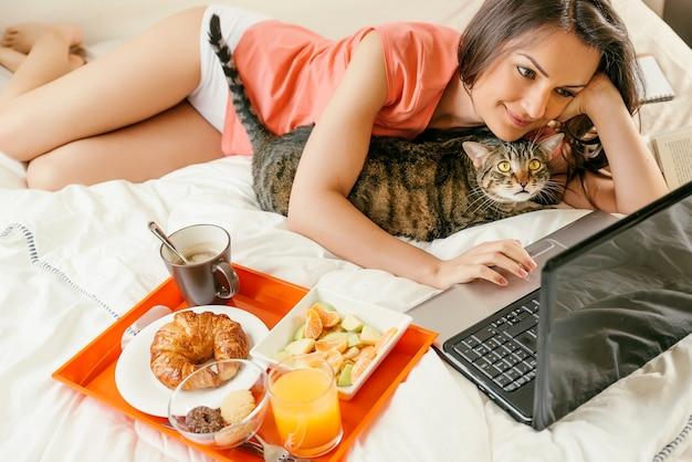 Kobieta oglądająca laptopa i jedząca śniadanie z kotem na łóżku