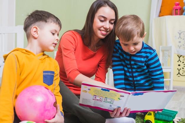 Kobieta oglądania książki z chłopcami