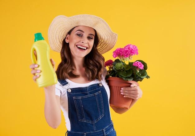 Kobieta ogrodniczka trzymająca nawóz i doniczkę z pelargonią