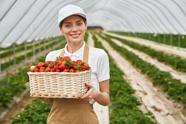 Kobieta ogrodniczka trzymająca wiklinowy kosz z truskawkami