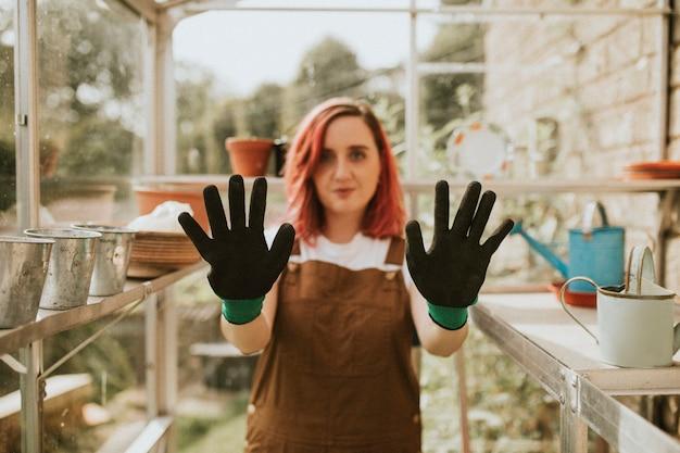 Kobieta ogrodniczka w czarnych rękawiczkach w szklarni