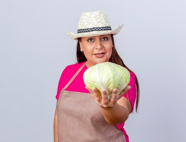 Kobieta ogrodniczka w średnim wieku w fartuchu i kapeluszu pokazująca kapustę uśmiechnięta pewnie