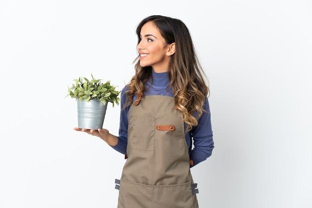 Kobieta ogrodnik gospodarstwa roślin na białym tle patrząc z boku i uśmiechnięty