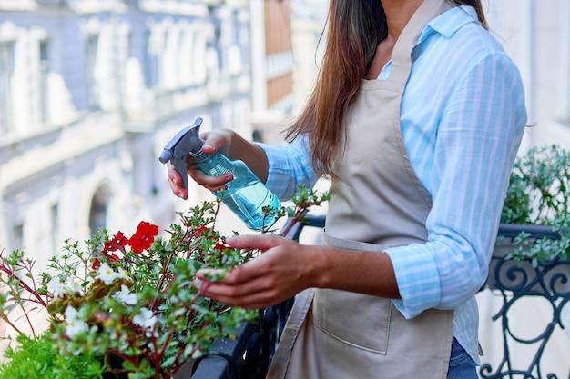 Kobieta ogrodnik podlewanie kwiatów balkonowych za pomocą butelki z rozpylaczem