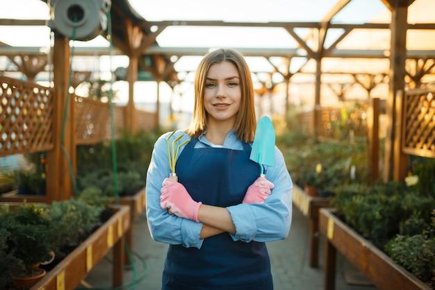 Kobieta ogrodnik pozuje w sklepie dla ogrodnictwa, sprzedawczyni. kobieta sprzedaje rośliny w kwiaciarni, sprzedawca w fartuchu i rękawiczkach