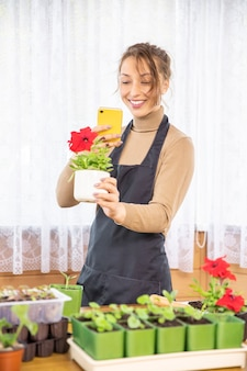 Kobieta ogrodnik robi zdjęcie kwitnącej rośliny petunii na telefon komórkowy