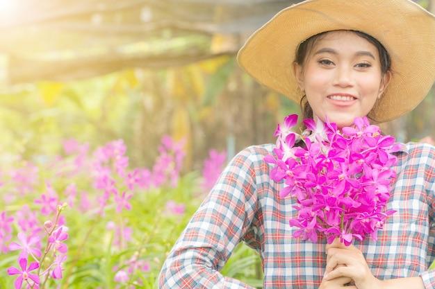 Kobieta ogrodnik ubrany w koszulę w kratę w kapeluszu trzyma różową orchideę w ręku.