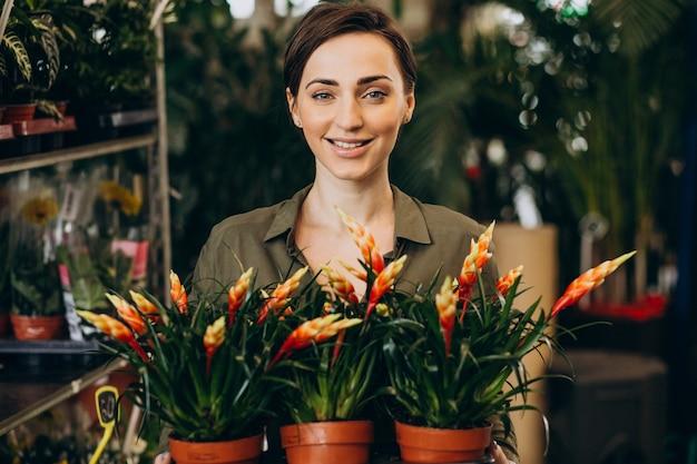 Kobieta ogrodnik w domu roślin z roślinami i kwiatami