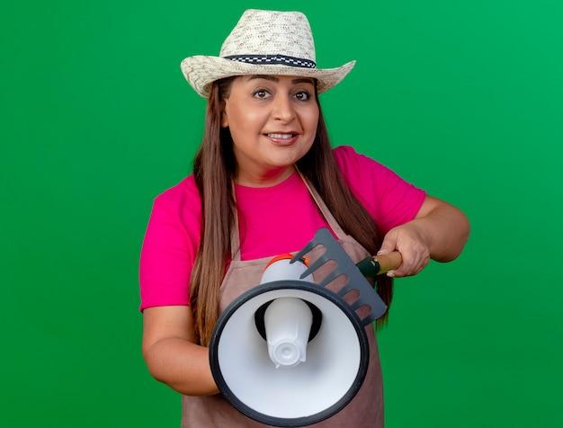 Kobieta ogrodnik w średnim wieku w fartuch i kapelusz gospodarstwa mini prowizji