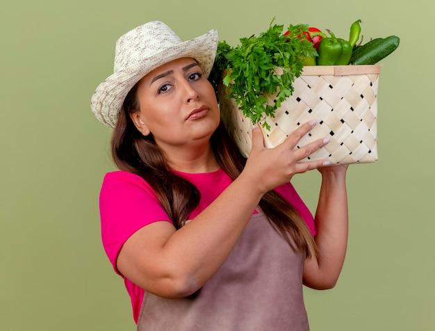 Kobieta ogrodnik w średnim wieku w fartuch i kapelusz, trzymając skrzynię pełną warzyw