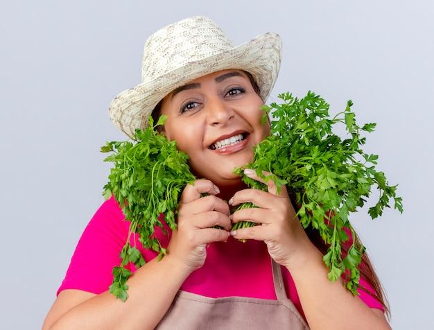 Kobieta ogrodnik w średnim wieku w fartuch i kapelusz, trzymając świeże zioła