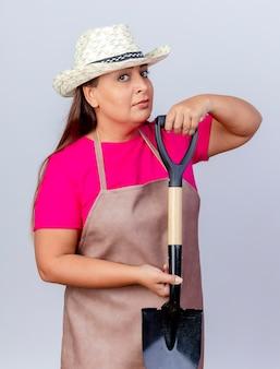 Kobieta ogrodnik w średnim wieku w fartuch i kapelusz wykazujące łopatę patrząc na kamery z poważną twarzą stojącą na białym tle