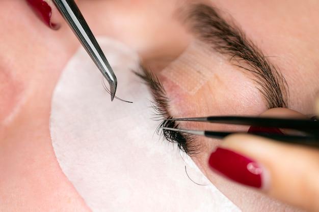 Kobieta oko z długimi rzęsami. przedłużanie rzęs. proces klejenia rzęs na oku. rzęsy, zbliżenie, wybrane skupienie.