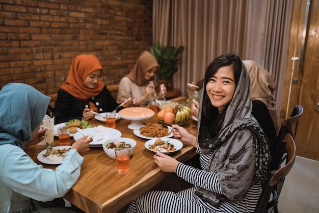Kobieta ono uśmiecha się gdy spojrzenie przy kamerą w jadalni