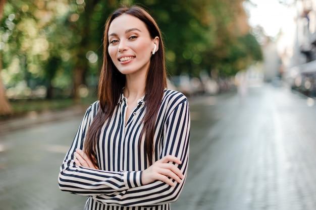 Kobieta ono uśmiecha się outdoors na ulicie z uszatymi strąkami