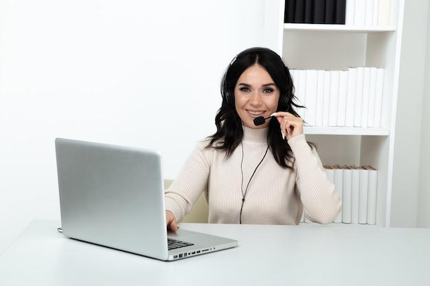 Kobieta operator call center siedzi w swoim miejscu pracy.