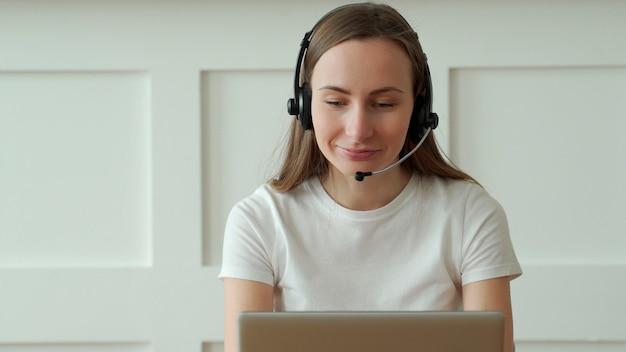 Kobieta operator pracuje z zestawem słuchawkowym i laptopem w call center