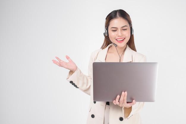 Kobieta operatora obsługi klienta w garniturze nosząca zestaw słuchawkowy na białym tle studio