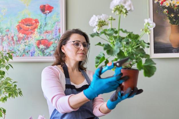 Kobieta opiekująca się kwiatem w doniczce w domu, usuwa liście sekatorów. hobby i wypoczynek, ogrodnictwo domowe, rośliny doniczkowe, miejska dżungla, koncepcja przyjaciół doniczkowych