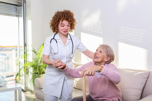 Kobieta opiekun pomaga starszy kobieta wstać z kanapy w salonie. uśmiechnięta pielęgniarka pomaga starszej kobiety wstawał.