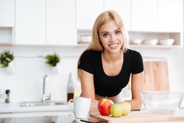 Kobieta opiera na stole podczas gdy stojący przy kuchnią