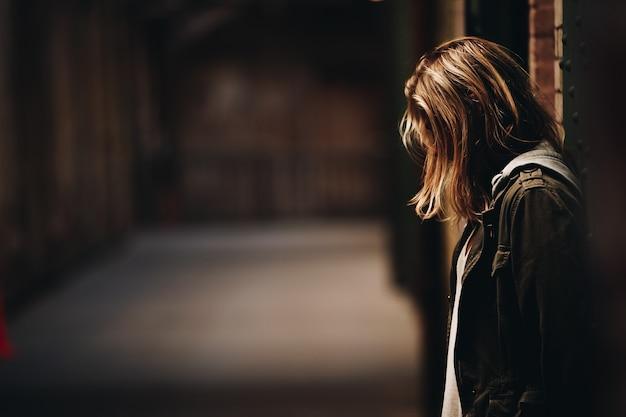 Kobieta opiera przeciw ścianie patrzeje w dół w korytarzu z zamazanym tłem w alcatraz wyspie