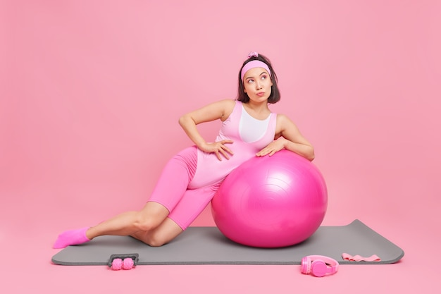 Kobieta opiera się na piłce fitness pozuje na karemacie pogrążona w myślach odizolowanych na różowo