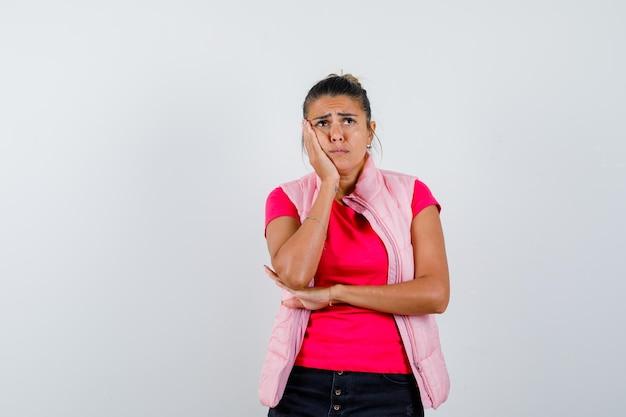Kobieta opierając policzek na dłoni w koszulce, kamizelce i smutno wygląda