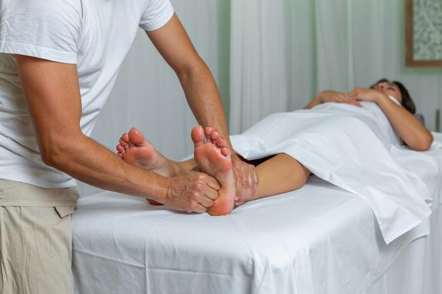 Kobieta opierając się na stole do masażu otrzymująca masaż refleksologii stóp przez nie do poznania męskiej kosmetyczki w spa. koncepcja spa.