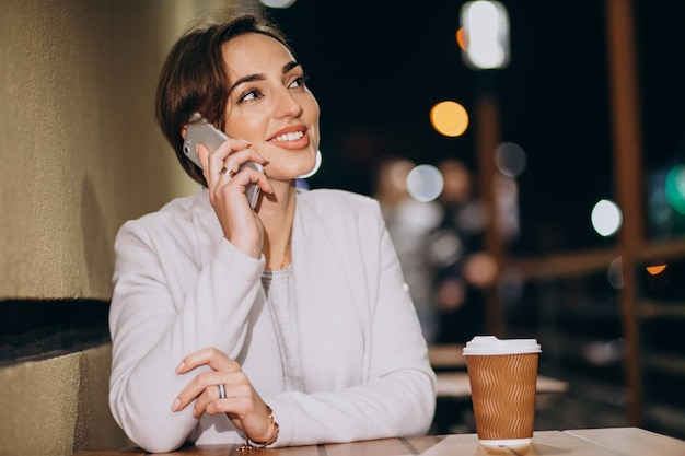 Kobieta opowiada na telefonie i pije kawę outside w ulicie przy nocą