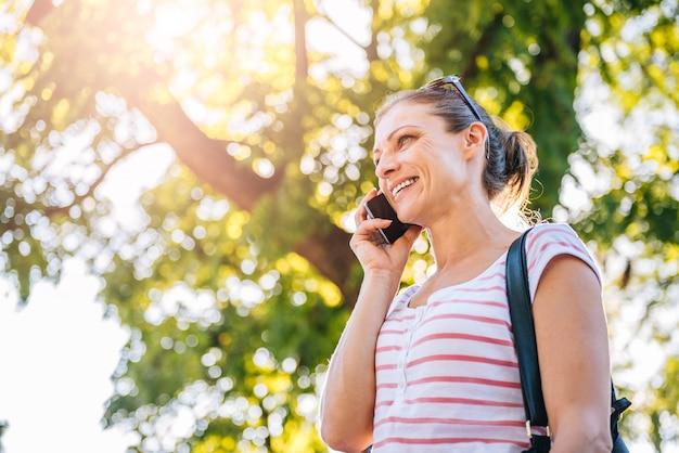 Kobieta opowiada na telefonie komórkowym w parku