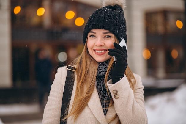 Kobieta opowiada na telefonie na zewnątrz kawiarni