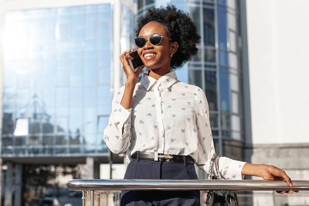 Kobieta opowiada nad telefonem z okularami przeciwsłonecznymi