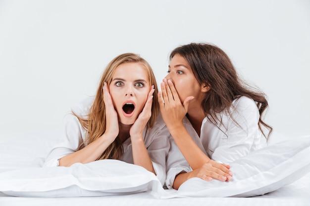Kobieta opowiada plotki swojej dziewczynie leżąc na łóżku z poduszkami