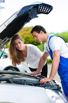 Kobieta opowiada samochodowy mechanik w remontowym sklepie